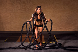 Social fitness girl posing with ropes in gym