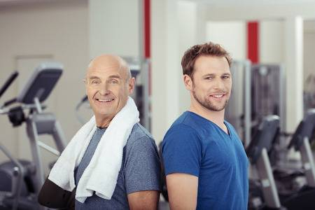 35556165 two fit healthy men posing back to back at the gym one senior and one young looking at the camera wi